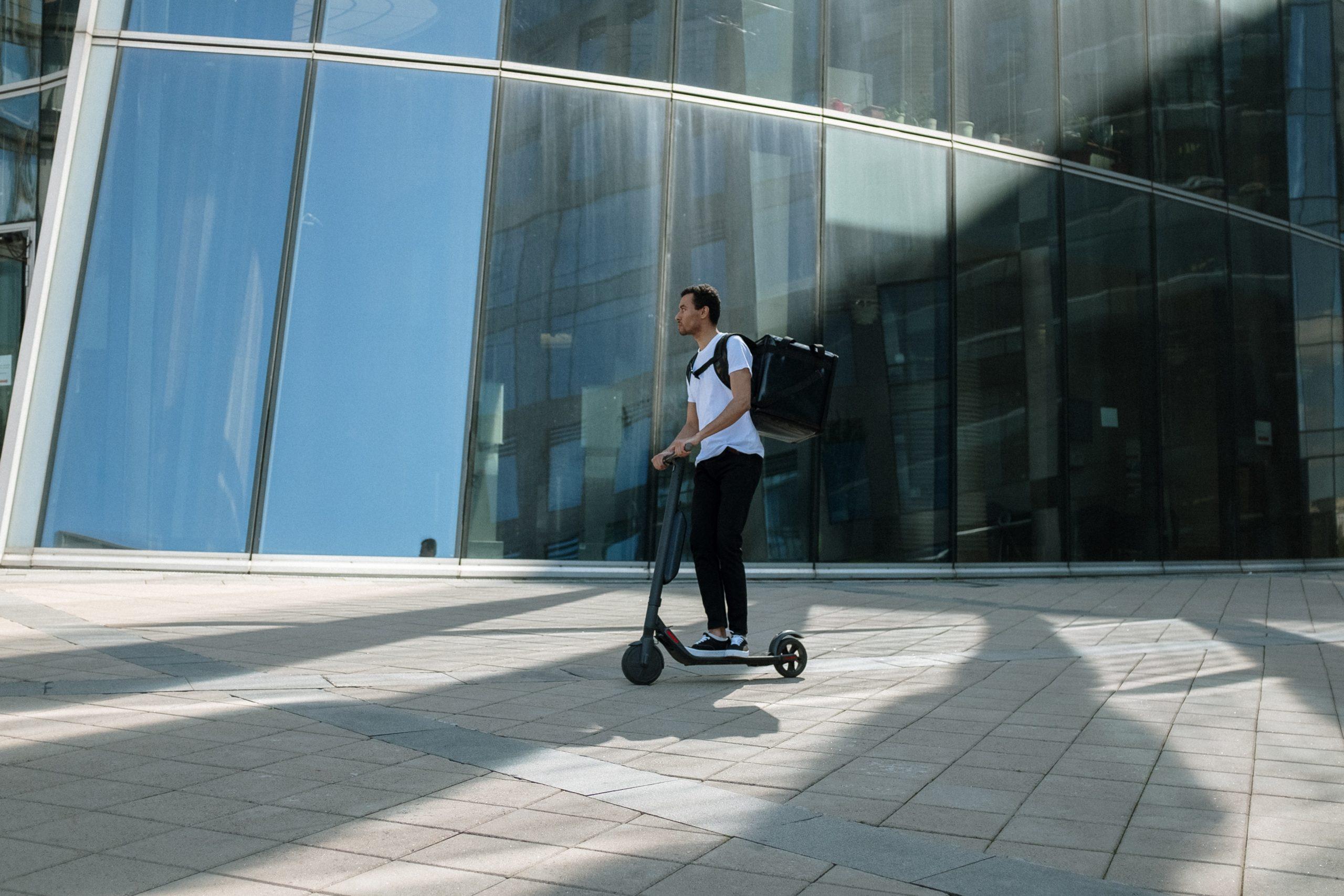 hombre en patinete eléctrico paseando con mochila